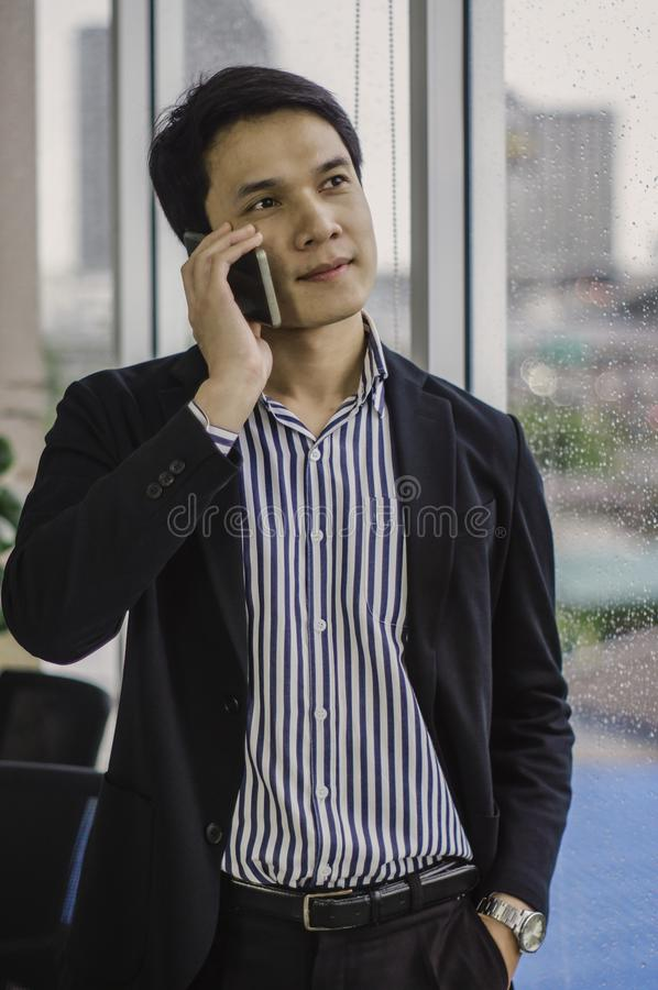亚洲由窗口的商人英俊的常设谈的智能手机,与在玻璃的下落雨在办公室 免版税库存照片