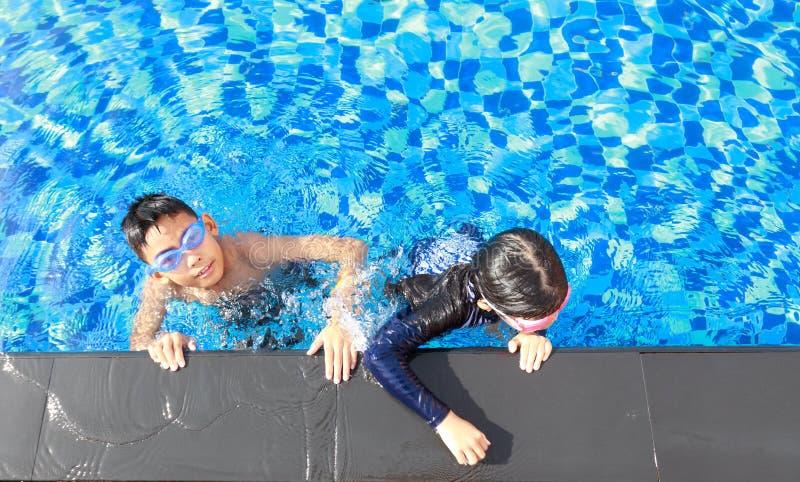 亚洲男孩和女孩游泳 库存照片