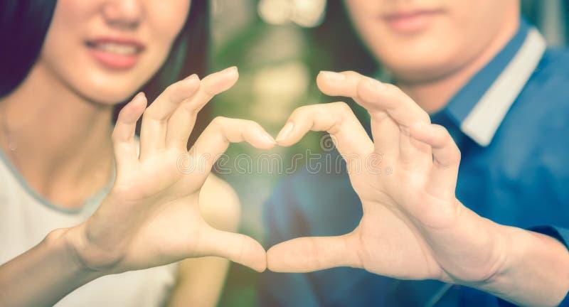 亚洲男性和女性夫妇象征有心脏嘘的手 库存图片