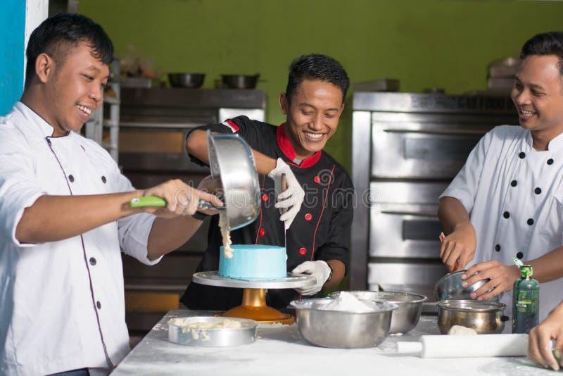 亚洲男性点心师愉快的工作队一起,当准备面团里面时 免版税库存图片