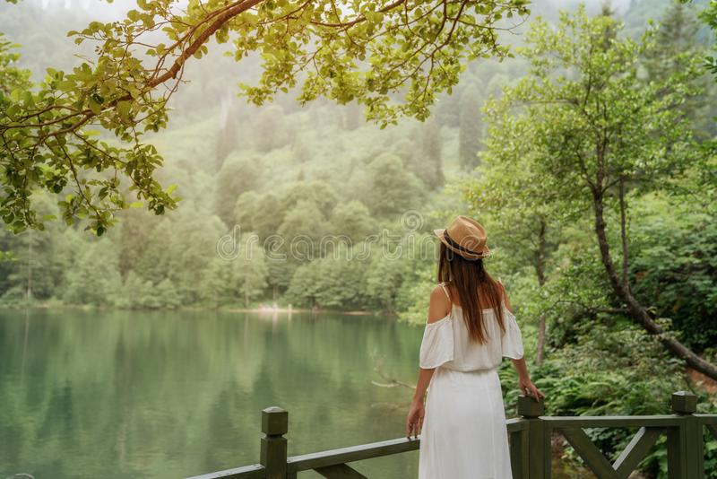 亚洲白种人中国走读女生愉快的湖混合户外外部公园纵向俏丽的种族微笑的春天夏天晴朗的妇女年轻人 少妇微笑愉快在晴朗的夏天或春日外面在公园由湖 免版税库存照片