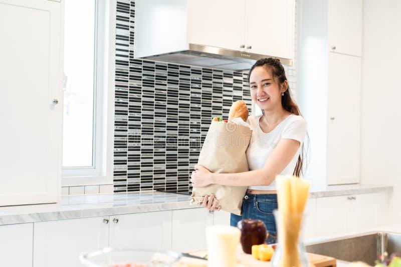 亚洲秀丽妇女藏品袋子烹调的成份在超级市场人和生活方式概念的购物以后 食物和 免版税库存照片