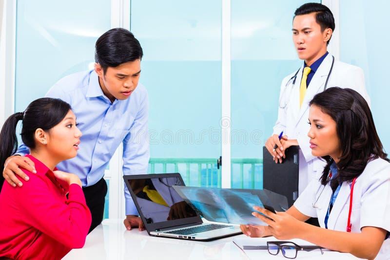 亚洲耐心咨询医生办公室 免版税库存图片