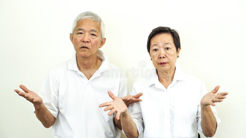 亚洲资深与问题姿态表示的夫妇不快乐的恼怒的成交 库存照片