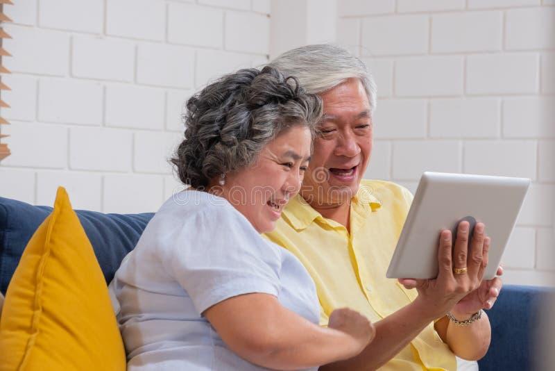 亚洲资深夫妇用途片剂视频通话和谈话对孙 库存照片