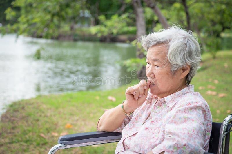亚洲资深妇女感觉在轮椅室外公园,老年人注重了,担心的女性叮咬手指甲以紧张 免版税库存照片