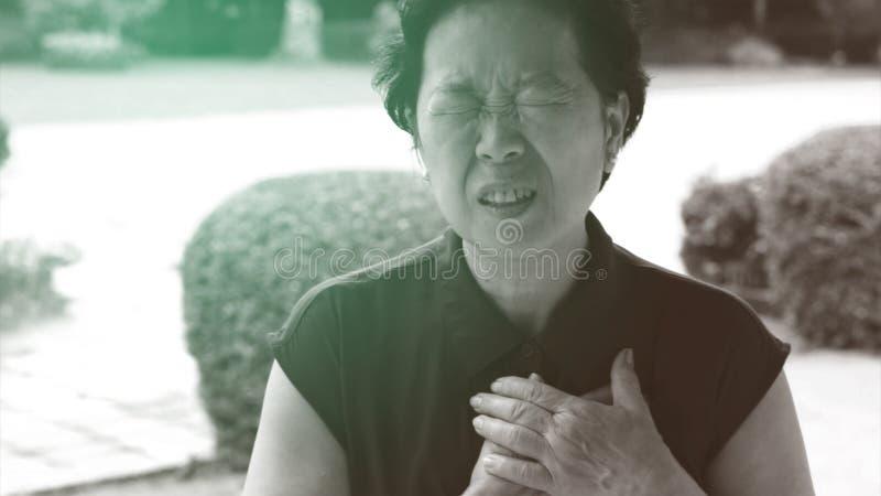 亚洲资深妇女胸口痛心脏攻击冲程医疗保健 库存图片