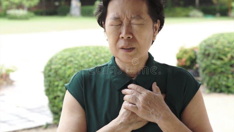 亚洲资深妇女胸口痛心脏攻击冲程医疗保健 免版税库存照片