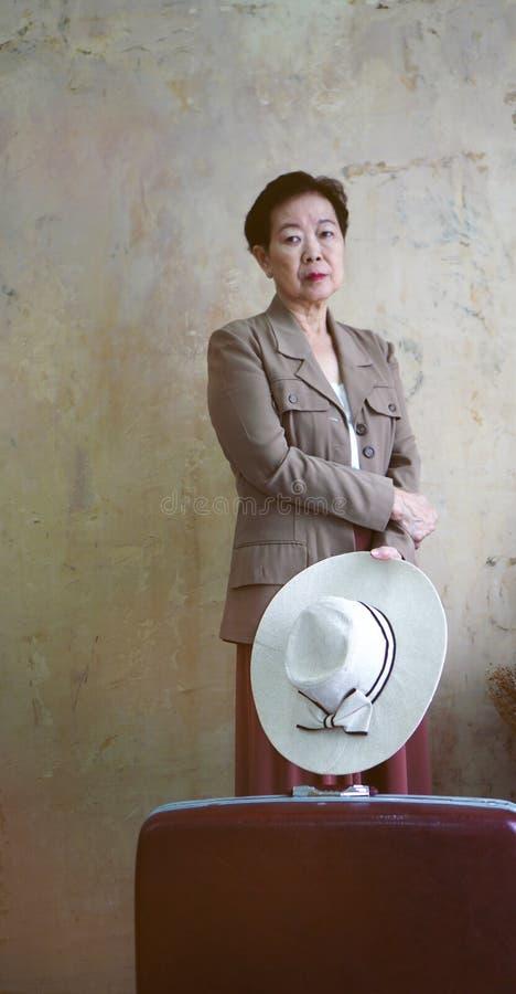 亚洲资深妇女葡萄酒帽子,与旅行luggag的减速火箭的时尚 免版税图库摄影