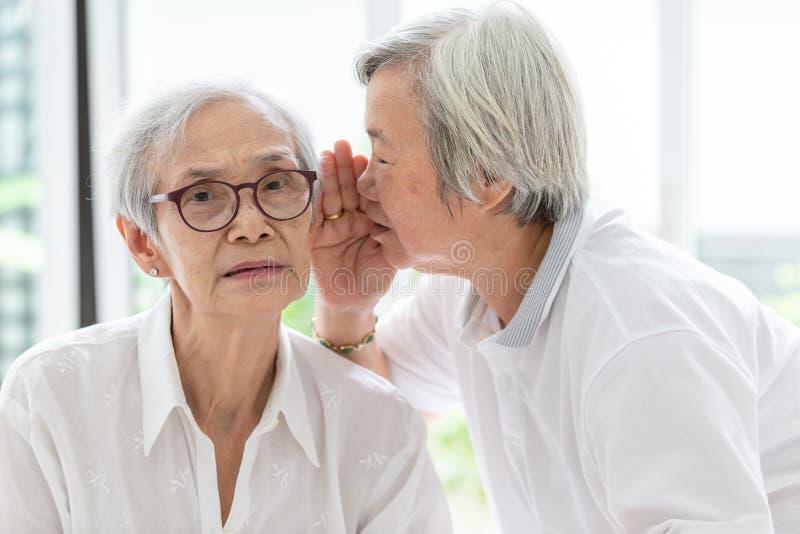 亚洲资深妇女藏品手在嘴在耳朵的告诉滑稽,闲话附近对朋友,讲话在年长妇女耳朵和在面孔附近, 免版税库存图片