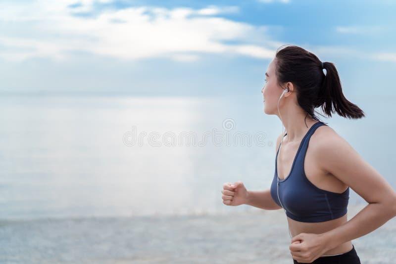 亚洲跑步的妇女健身锻炼室外在日落的海滩 免版税库存图片