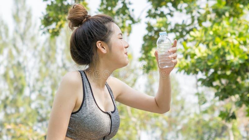 亚洲逗人喜爱的体育健康适合和牢固的亭亭玉立的青少年的女孩喝水 免版税库存照片