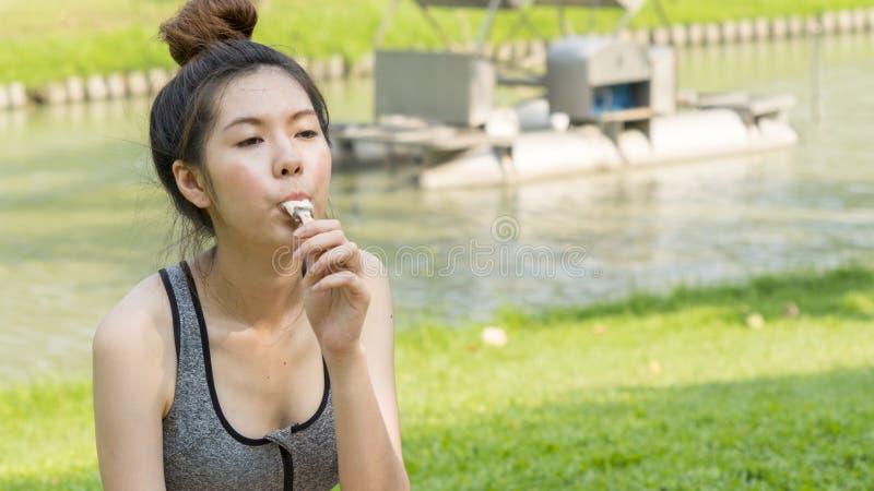 亚洲逗人喜爱的体育健康青少年的女孩吃冰淇凌 免版税库存图片