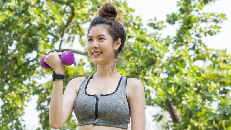 亚洲逗人喜爱的健康适合和牢固的亭亭玉立的女孩愉快对站立的工作 免版税库存照片