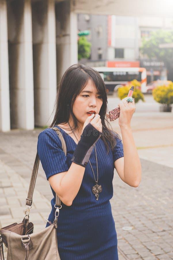 亚洲逗人喜爱的女孩构成和申请唇膏 图库摄影