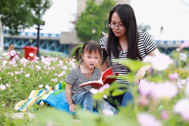 亚洲逗人喜爱的笑可爱的可爱的女孩读了与母亲的书享受与妈妈的自由天讲故事室外在夏天公园愉快的微笑 免版税库存照片