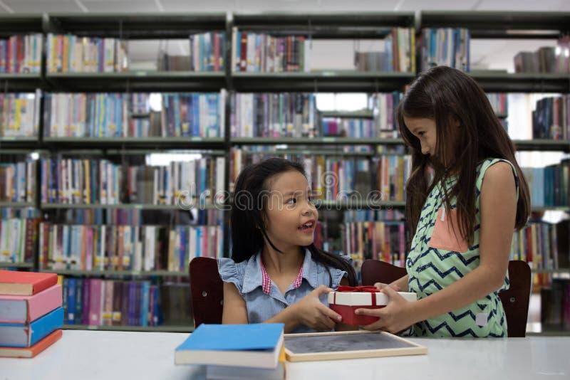 亚洲逗人喜爱的给giftbox的夫妇年轻学校女孩在图书馆里 免版税库存照片