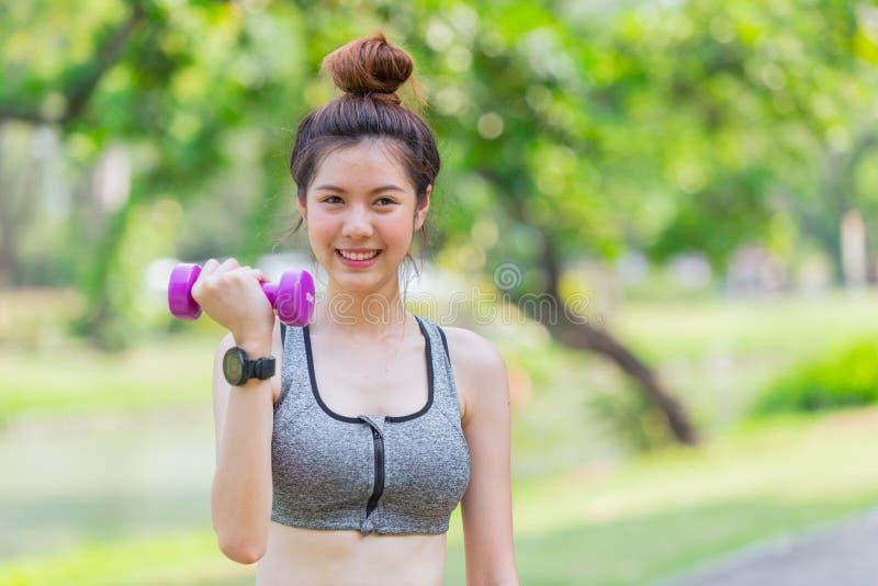 亚洲逗人喜爱青少年亭亭玉立和健康享受与小哑铃的二头肌锻炼 免版税图库摄影