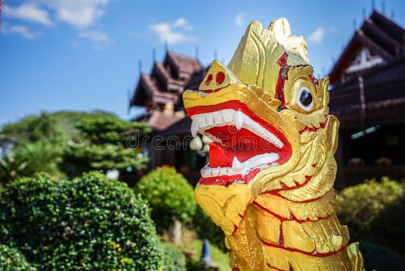 亚洲金红色狮子雕象有寺庙背景 免版税库存照片