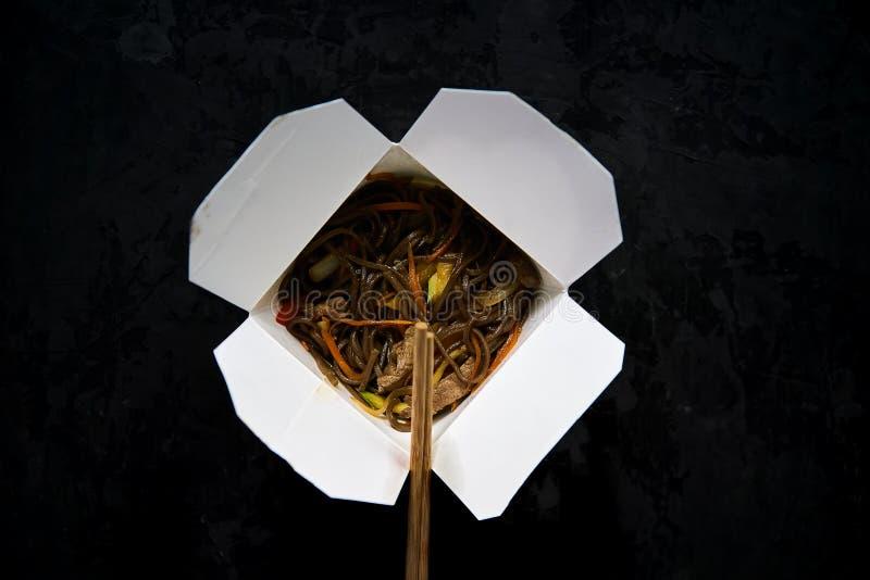 亚洲餐馆食物交付 索瓦面条用肉、菜和酱油在白色外卖纸箱在黑背景w 免版税库存图片