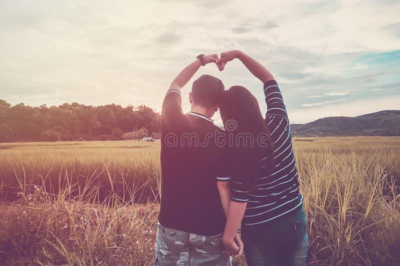 亚洲,浪漫夫妇或同性恋,女性爱开放胳膊,心脏标志愉快在与日落,情人节的米领域 免版税库存照片