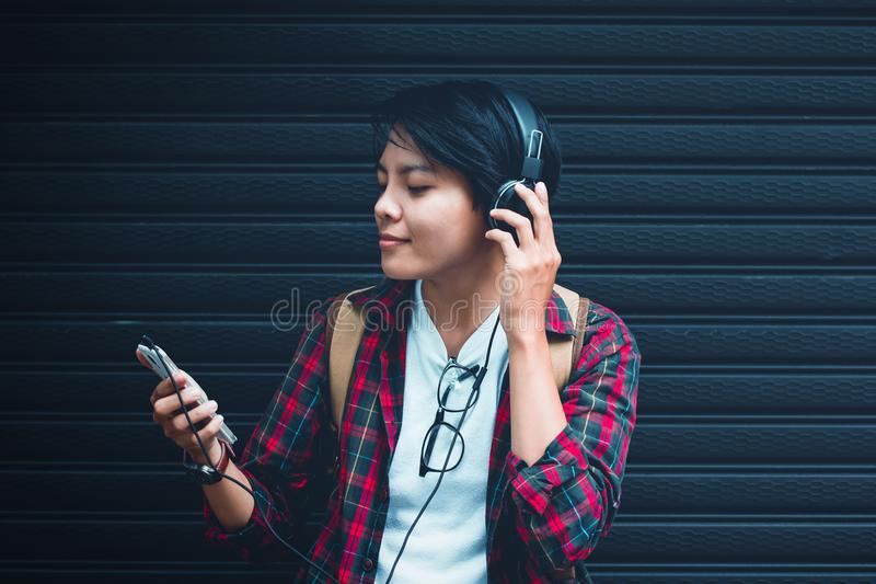 亚洲 十几岁听到音乐在与葡萄酒口气的近距离 免版税库存图片