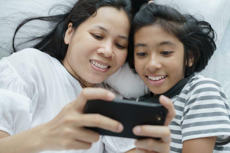 亚裔一起打与电话的母亲和女儿比赛在床上 愉快的妇女和的女孩和乐趣在卧室 库存图片