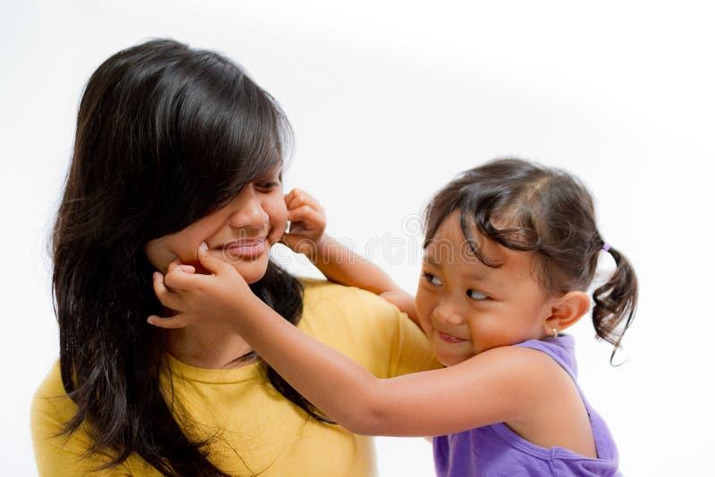 亚裔与青少年的姐妹的儿童愉快的使用的少量面颊 免版税图库摄影
