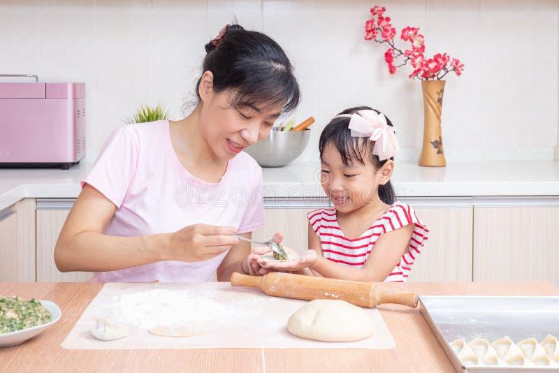 亚裔中国做饺子的母亲和女儿在厨房里 免版税库存图片