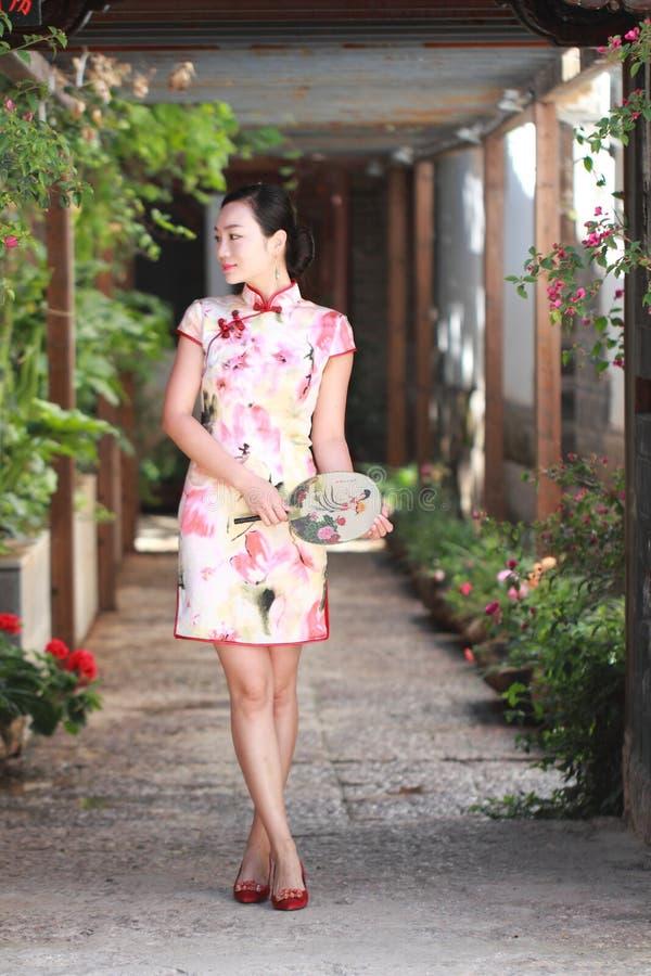 亚裔中国女孩在古镇佩带cheongsam享受业余时间 库存照片