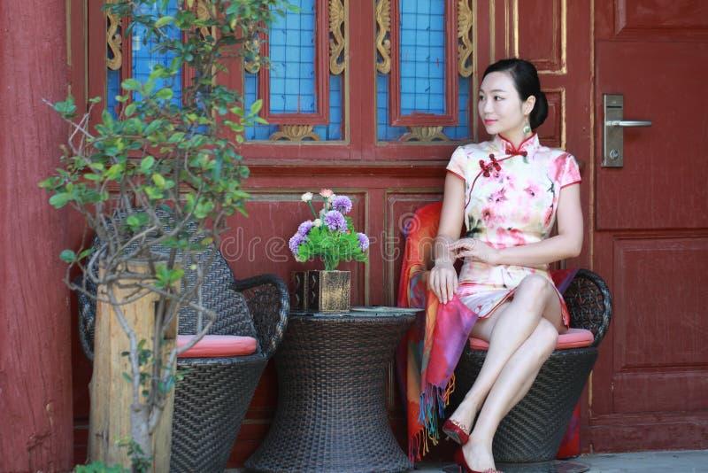亚裔中国女孩在lijiang古镇佩带cheongsam享受假日 免版税库存图片