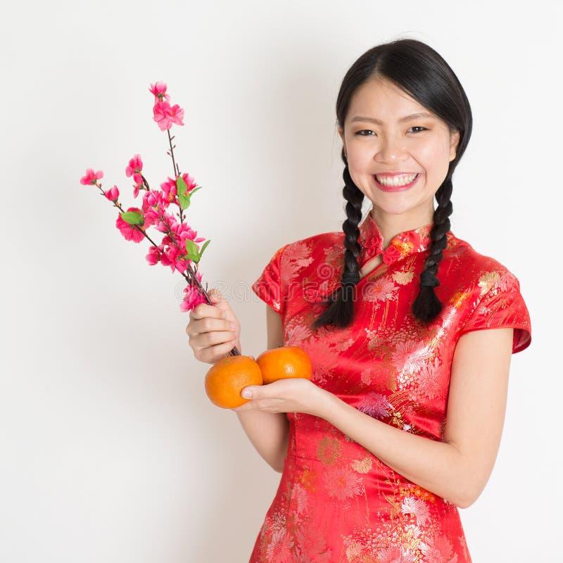 亚裔中国女孩拿着蜜桔的和李子开花 库存照片