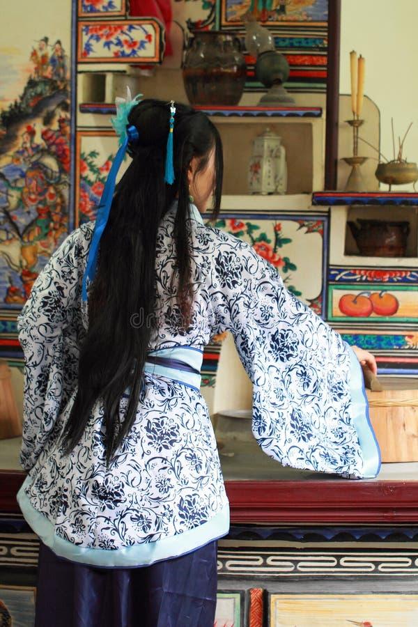 亚裔中国女孩画象传统礼服的,在一个古老厨房里佩带蓝色和白色瓷样式Hanfu,厨师 免版税库存图片