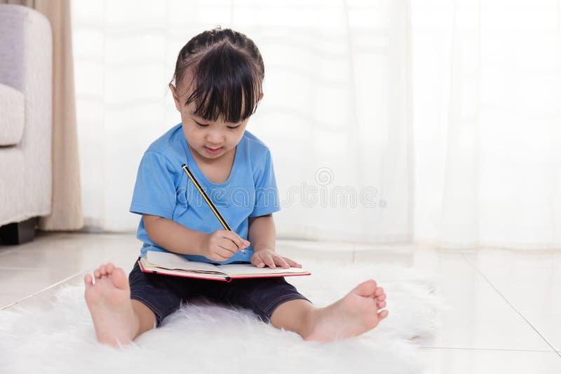 亚裔中国小女孩坐地板图画 免版税库存图片