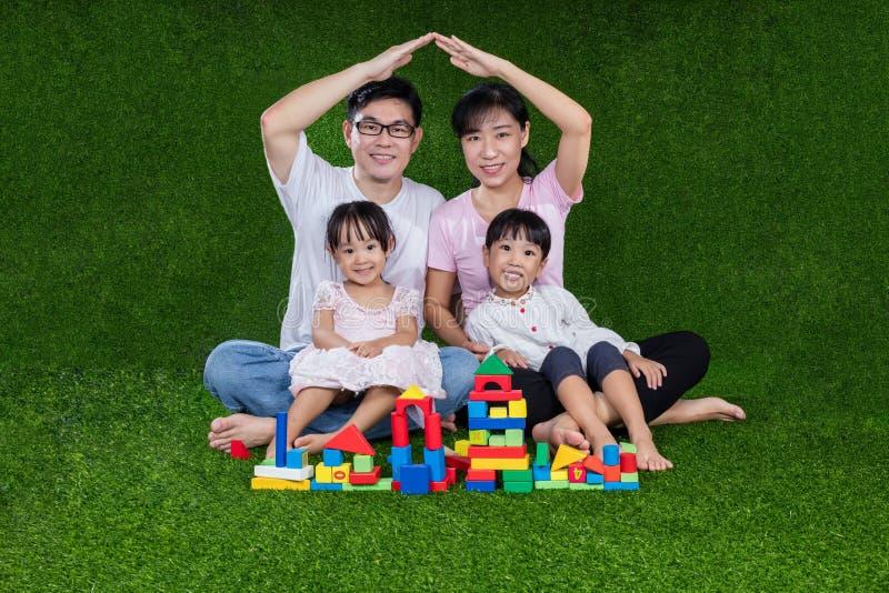 亚裔中国演奏在草的父母和女儿块 免版税库存照片