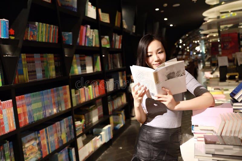 亚裔中国美丽的相当年轻逗人喜爱的妇女女学生少年读了在书店图书馆微笑的书花费她的消遣 免版税库存照片