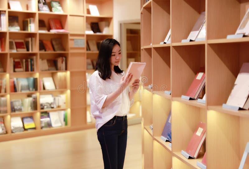 亚裔中国美丽的相当逗人喜爱的妇女女学生少年在书店图书馆里读了书 免版税库存照片