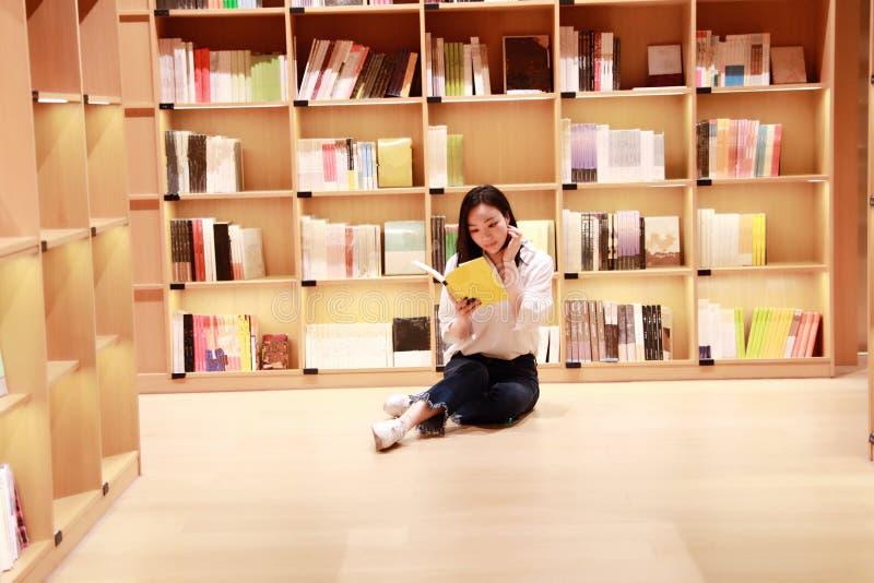 亚裔中国美丽的相当逗人喜爱的妇女女学生少年在书店图书馆里读了书 免版税库存图片