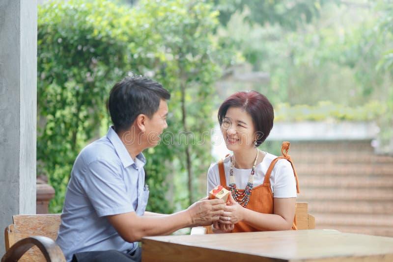 亚裔中年人给一个礼物他的周年婚礼的妻子 免版税库存照片