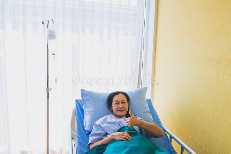 亚裔中年妇女患者焦点在床上的治疗的在屋子医院里 免版税库存图片