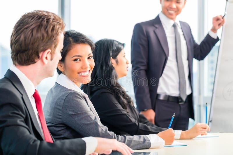 亚裔买卖人在办公室队会议 免版税库存图片