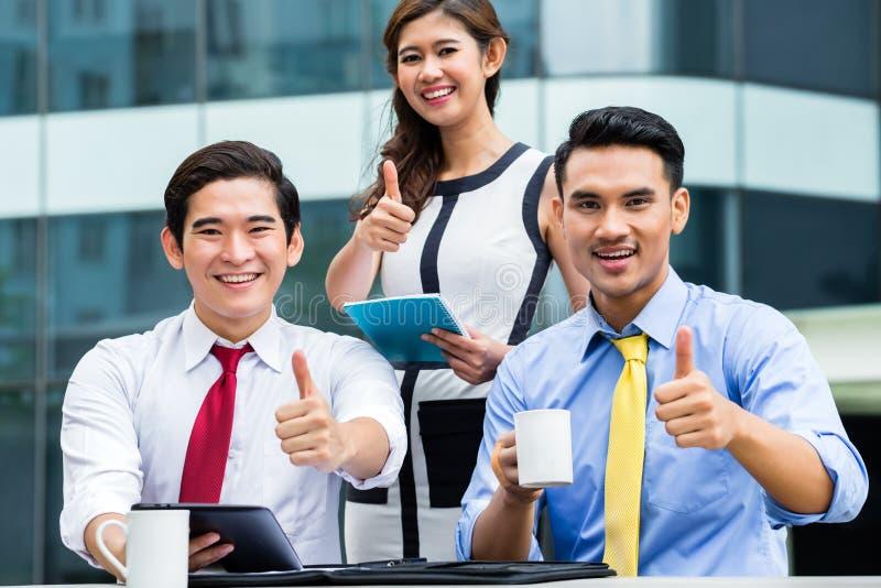 亚裔买卖人外面与咖啡一起使用 库存图片