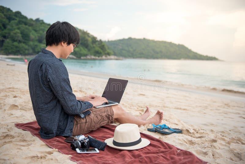 年轻亚裔人与在海滩的膝上型计算机一起使用 库存照片