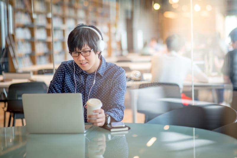 年轻亚裔人与膝上型计算机一起使用在图书馆里 库存照片