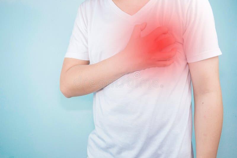亚裔人使用手拿着他们的心脏 显示从心脏疾患,心脏攻击症状医疗保健和医疗概念的痛苦 库存照片
