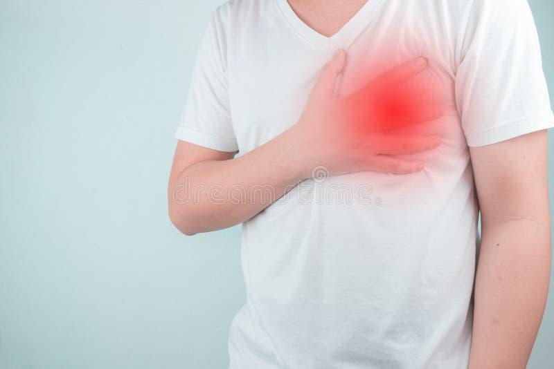 亚裔人使用手拿着他们的心脏 显示从心脏疾患,心脏攻击症状医疗保健和医疗概念的痛苦 图库摄影