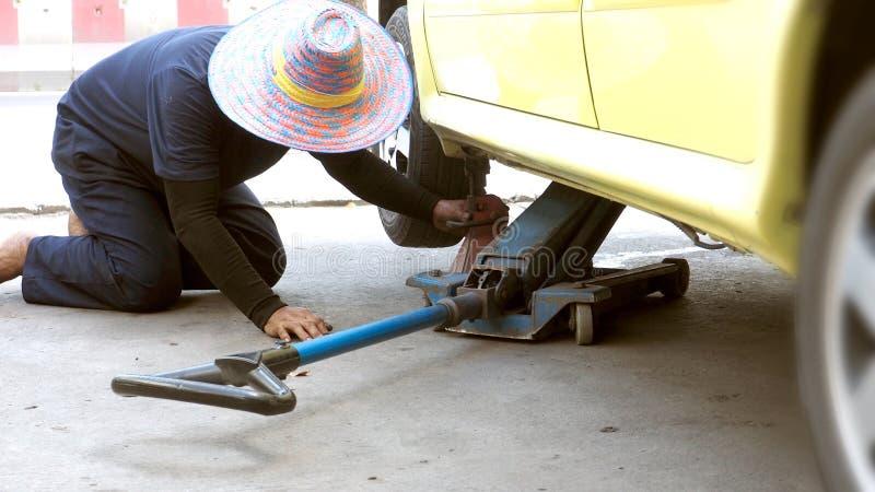 亚裔人做了对象对晃动台车起重器服务汽车 免版税库存图片