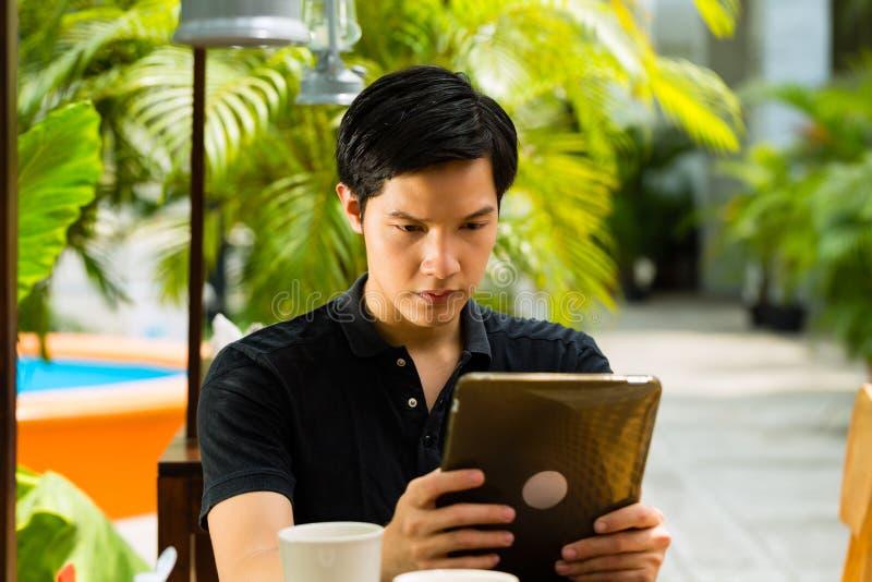 亚裔人在室外的酒吧或的咖啡馆坐 免版税图库摄影