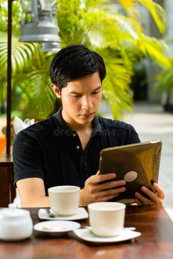 亚裔人在室外的酒吧或的咖啡馆坐 免版税库存图片