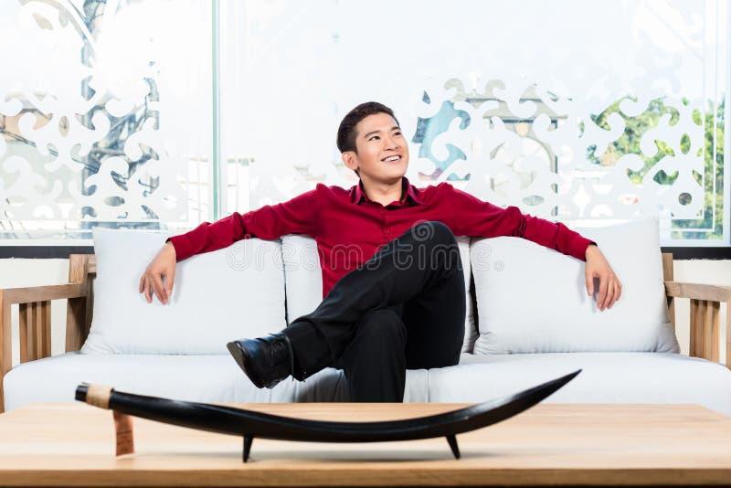 亚裔人坐在家具店的沙发 库存图片